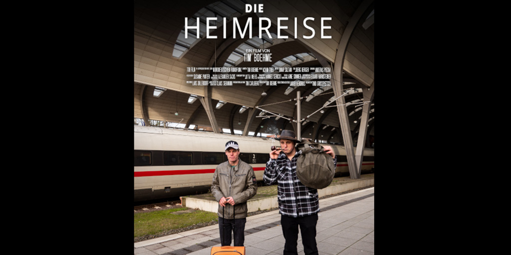 """Ausschnitt aus dem Filmplakat """"Die Heimreise"""" Zwei Männer in einer Bahnhofshalle"""