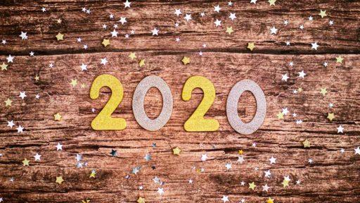Foto der Ziffern 2020 auf Holzunterlage, umgeben von glitzernden Sternchen (Symbolbild)